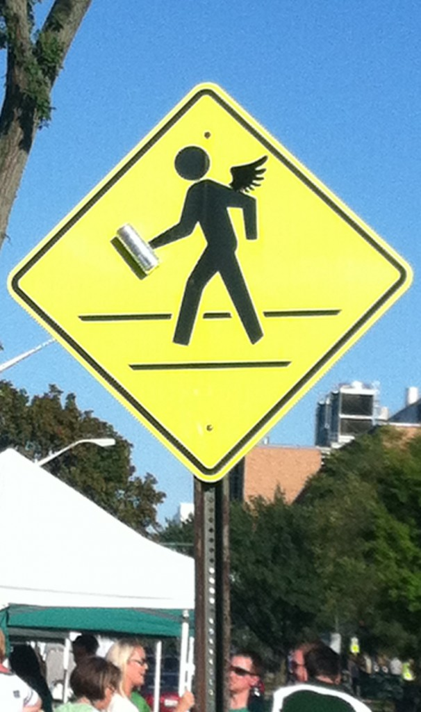 A pedestrian crossing sign with a pair of wings and a Red Bull can added on.