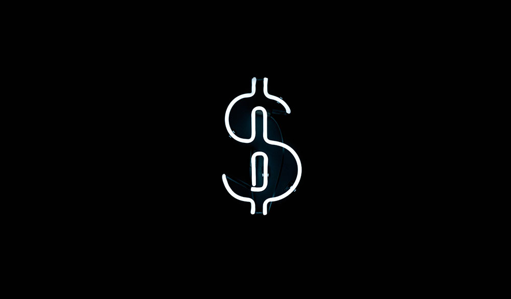 A white neon dollar sign against a black wall