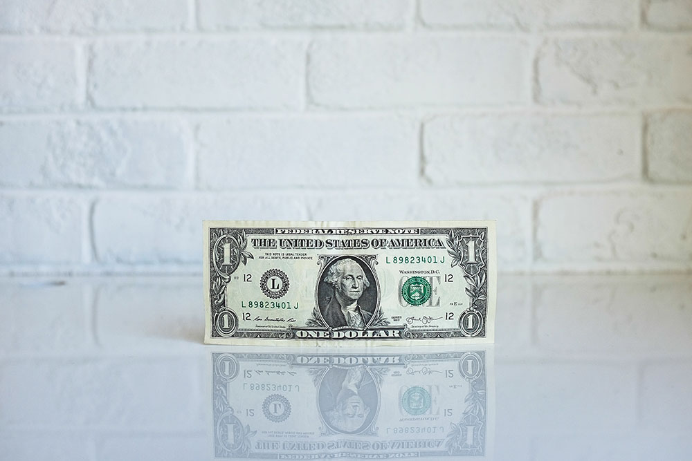 A one dollar bill on a white table with a white brick wall in the background