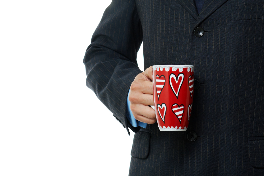 A man in a business suit holding a coffee mug with hand drawn hearts on it.