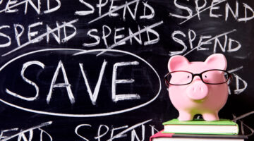 Pink piggy bank with glasses standing on books next to a blackboard with untidy spending and saving message.