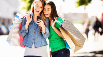 Appealing to Millennials: Happy young female friends with shopping bags using smart phone while standing on street.
