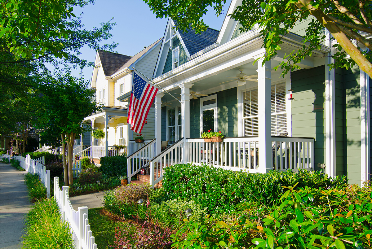 The quintessential American Dream: A house with a white picket fence and American flag hanging from the porch