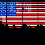 The concept of the American Dream has been challenged: A digital version of the United States flag on a large screen