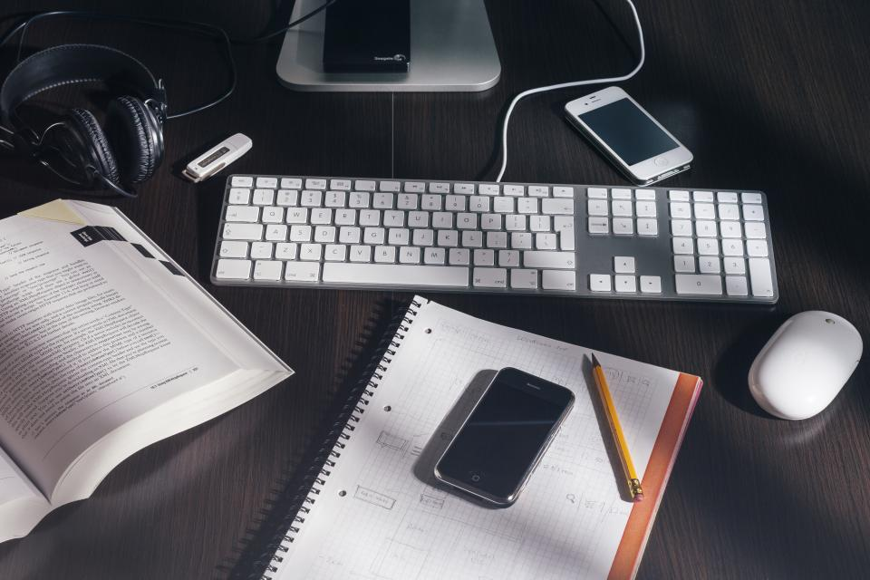 A desk covered with items--a smartphone, keyboard, book, notebook, headphones, flashdrive, mouse, and the base of a monitor--demonstrates an individual example of our connected society.