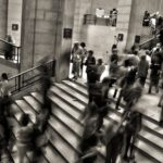 Financial anxiety can feel like a busy stairwell in black and white, people passing through are blurry