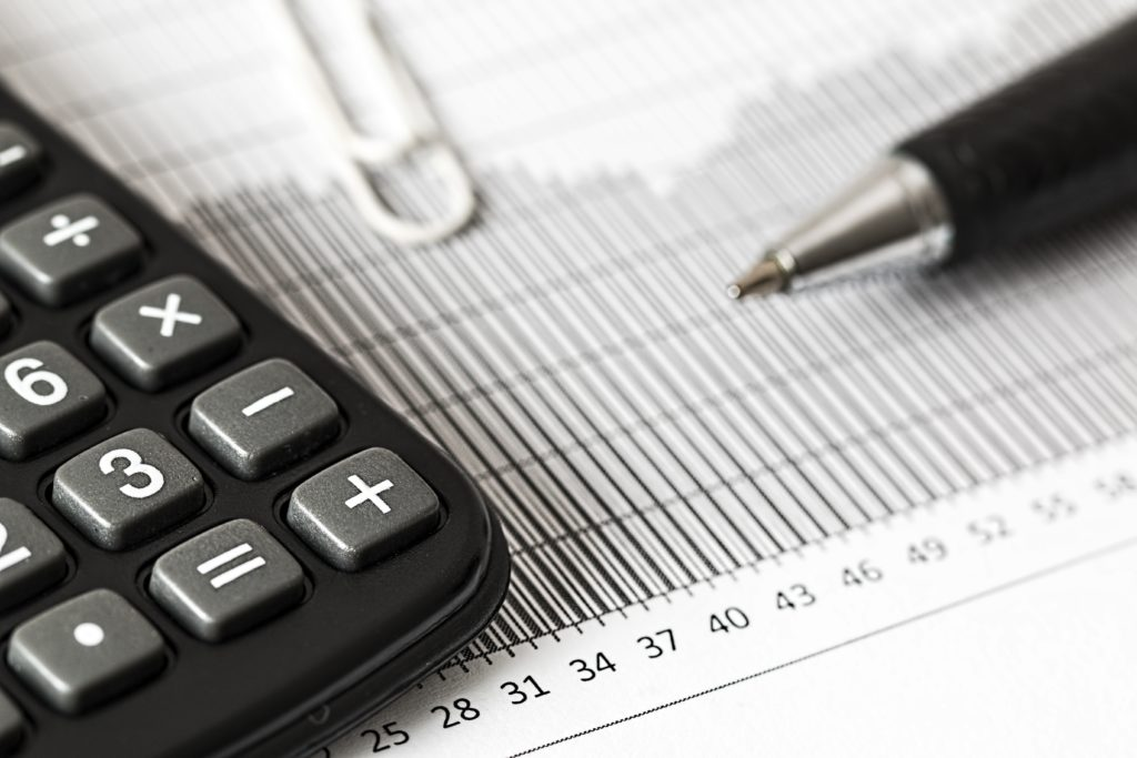 Reduce financial anxiety by staying engaged with your finances. Pictured: calculator and a pen on top of a chart