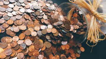 Hundreds of pennies pouring out of a jar