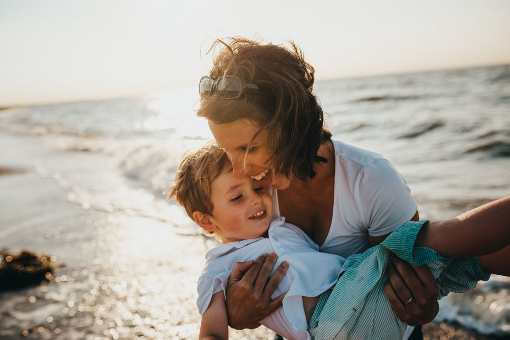 Women in finance: Women can only feel financially secure when their loved ones are taken care of. Here a woman carries her son on the beach--both are smiling