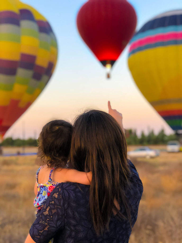 Women in Finance: women focus on investing to achieve specific goals that impact people important in their lives: their education, their children's education, or their retirement. Here, a woman points out a hot air balloon to her daughter