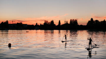 Health and Wealth: Illustrating a balance between the two with a photo of two people paddle boarding on a lake at sunset