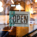 "Business owners optimistic: A sign reading ""Yes, we're open"" hangings inside a glass window"