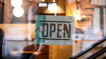 """Business owners optimistic: A sign reading """"Yes, we're open"""" hangings inside a glass window"""