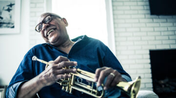 An older man sits on a chair, his head tilted back in laughter, a trumpet in his hands