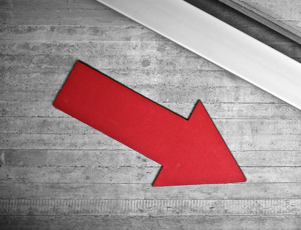 Red arrow on a wall pointing down