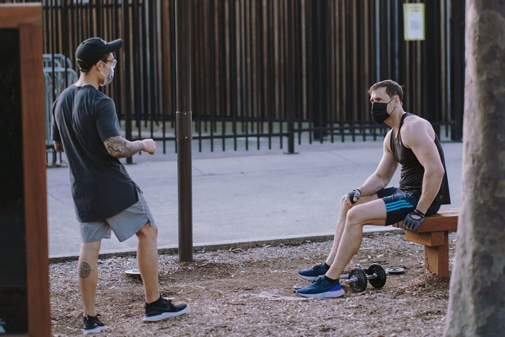 Two men in a public park talking at a safe distance, both wearing masks