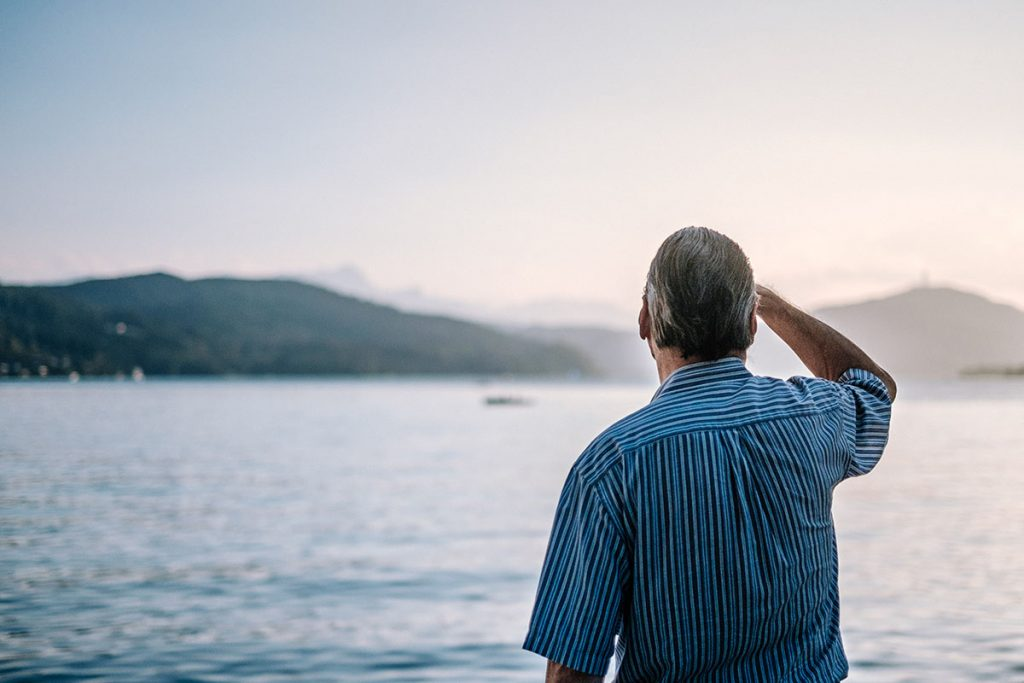 A gray-haired man looks out over a lake, hills beyond, his right hand shading his brow