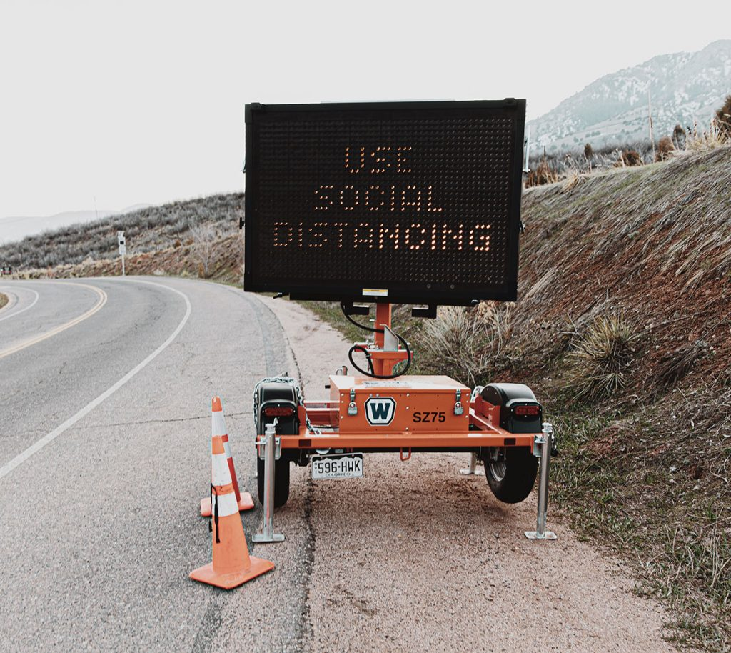 "A digital street-side sign reads ""use social distancing"""