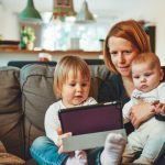 A woman holds a baby on a couch while a toddler sitting next to her holds a tablet. All of them are looking at the tablet, perhaps for a video chat.