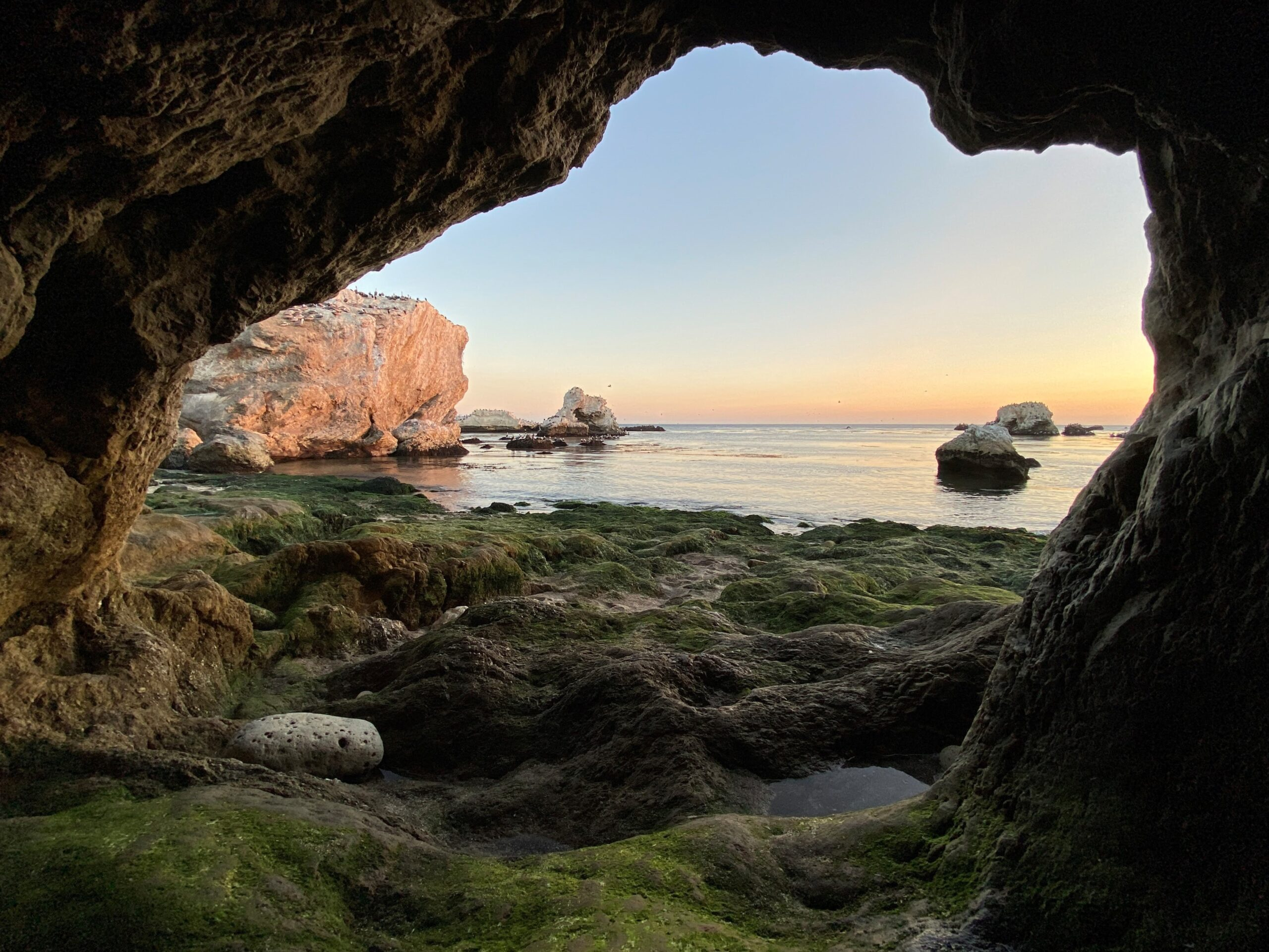 A photo of a cave opening that leads to the seashore